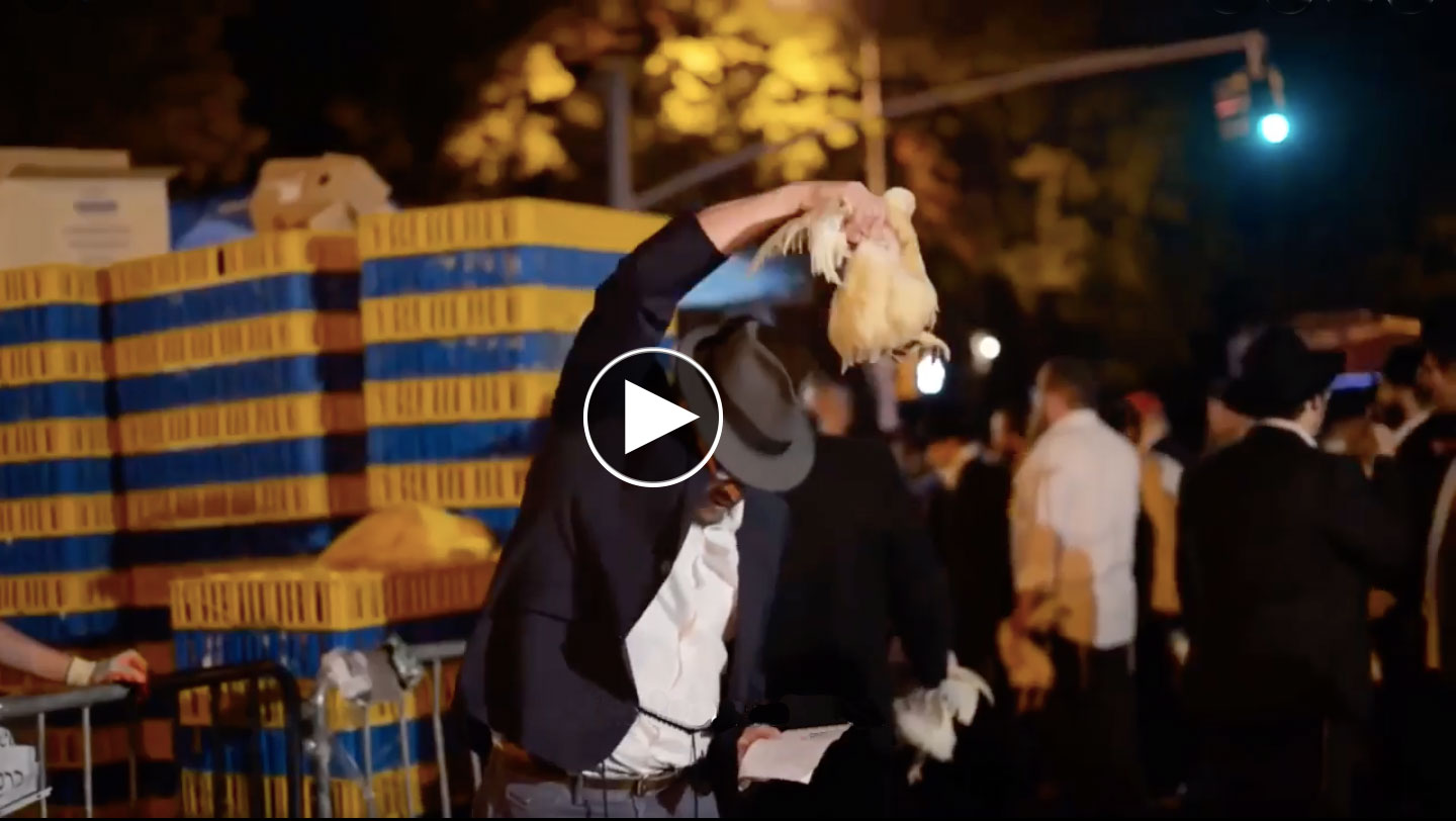 Man waving a chicken over his head while reading from notes