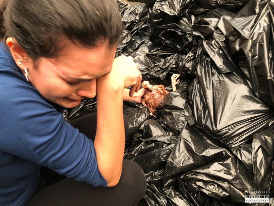 Crying woman reaching for a chicken in the garbage
